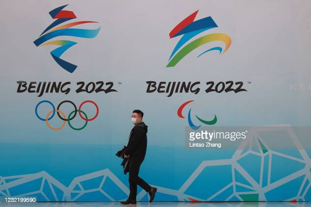 Chinese man wears a protective mask as he walk in front the logos of the 2022 Beijing Winter Olympics at National Aquatics Centre on April 9, 2021 in...