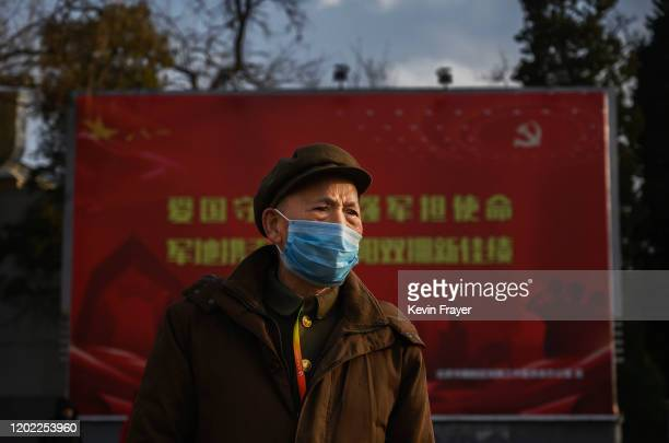 Chinese man wears a protective mask as he walks by a propaganda billboard at a normally busy intersection on February 21 2020 in Beijing China The...