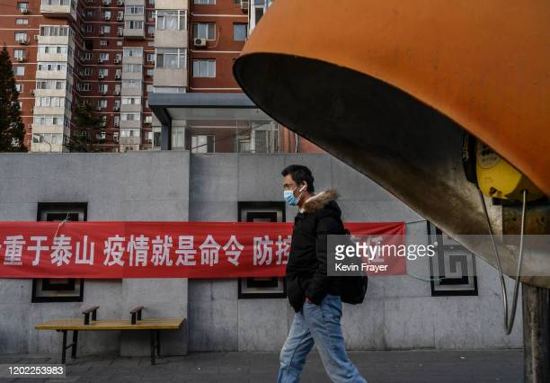 Chinese man wears a protective mask as he walks by a propaganda banner related to the coronavirus outbreak on a residential building on February 21...