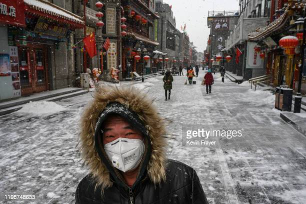 Chinese man wears a protective mask as he walks during a snowfall in an empty and shuttered commercial street on February 5 2020 in Beijing China...