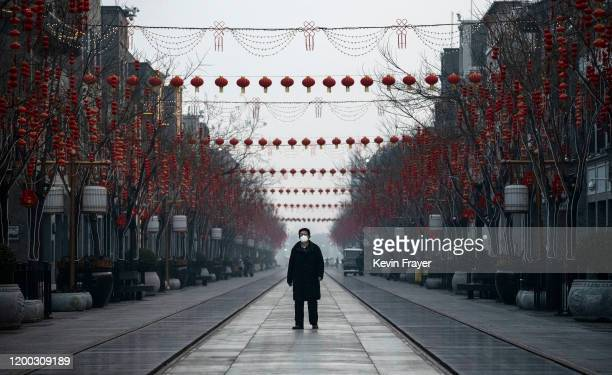 Chinese man wears a protective mask as he walks in a nearly empty and shuttered commercial street on February 12 2020 in Beijing China The number of...
