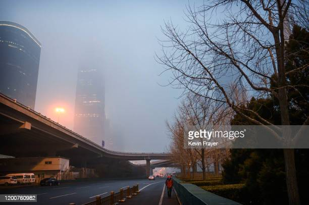 Chinese man wears a protective mask as he walks on a nearly empty road during rush hour in the central business district on February 13 2020 in...