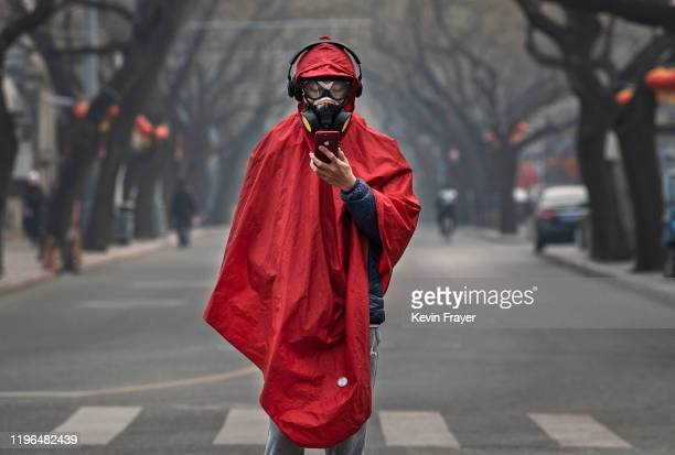 Chinese man wears a protective mask goggles and coat as he stands in a nearly empty street during the Chinese New Year holiday on January 26 2020 in...