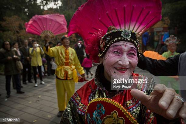 Chinese man wears a traditional costume during a performance as part of a morning exercise routine at a local park on November 15, 2015 in Beijing,...
