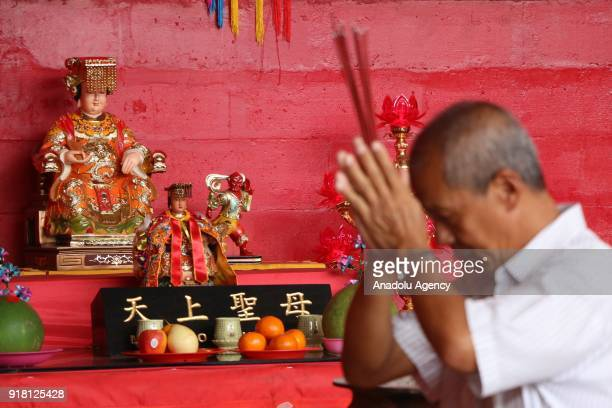 Chinese man who lives in Indonesia burns incense sticks as he prays for fruitfulness luck revenue as part of the beginning of the Year of the Dog...