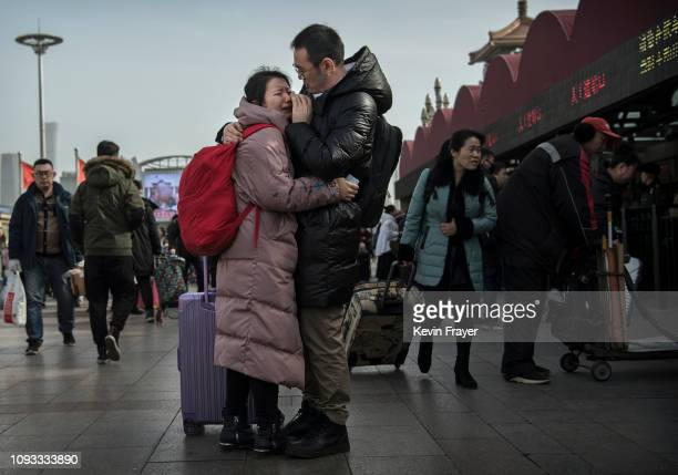 Chinese man wipes away a tear from the face of his partner as she prepares to leave him to visit family for the holiday at Beijing Railway Station on...