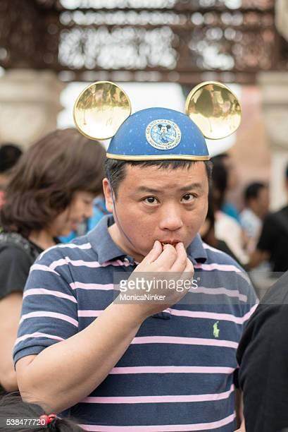 china hombre con sombrero mickey mouse - mickey mouse fotografías e imágenes de stock
