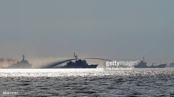 A Chinese Maritime Police Bureau ship uses water canon to harass a Vietnamese fisheries surveillance force vessel near the disputed Paracel Islands...
