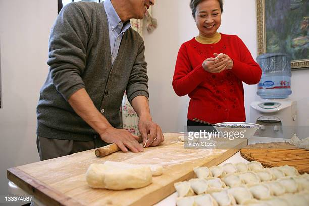 Chinese mature couple making chinese dumpling on New years Eve