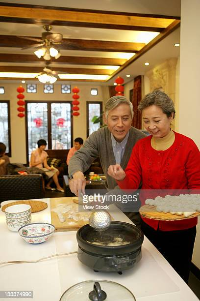 chinese mature couple making chinese dumpling on new years eve - 25 29 years stock pictures, royalty-free photos & images
