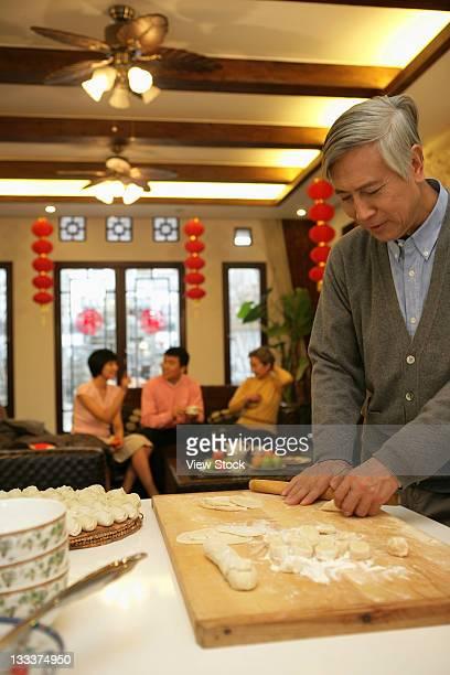 Chinese mature man make Chinese dumpling on New Years Eve