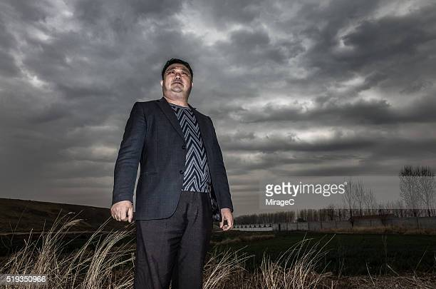 Chinese Mature Man Standing Against Stormy Sky