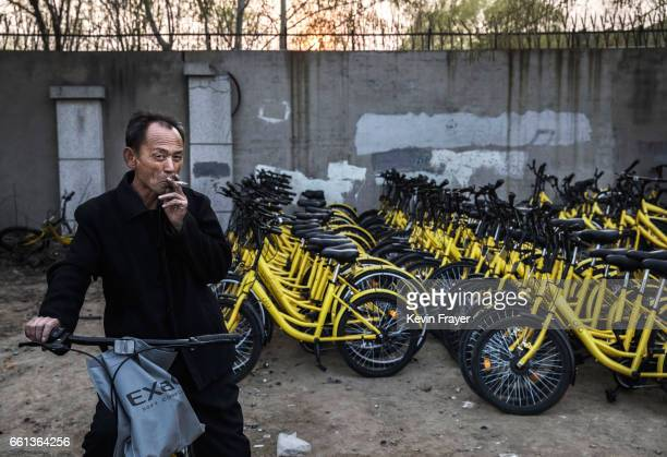 Chinese mechanic from bike share company Ofo Inc is seen next to damaged bicycles pulled off the streets at a repair depot for the company on March...