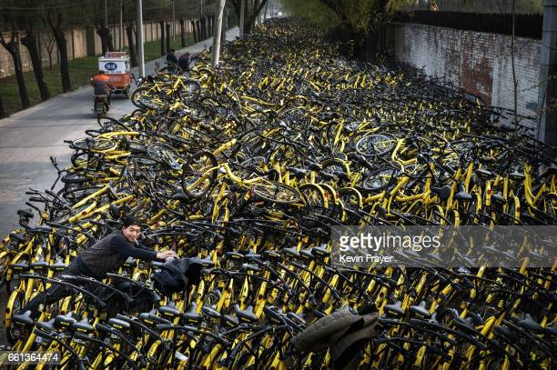 Chinese mechanic from bike share company Ofo Inc leans over a pile of thousands of damaged bicycles that were pulled off the streets where they are...