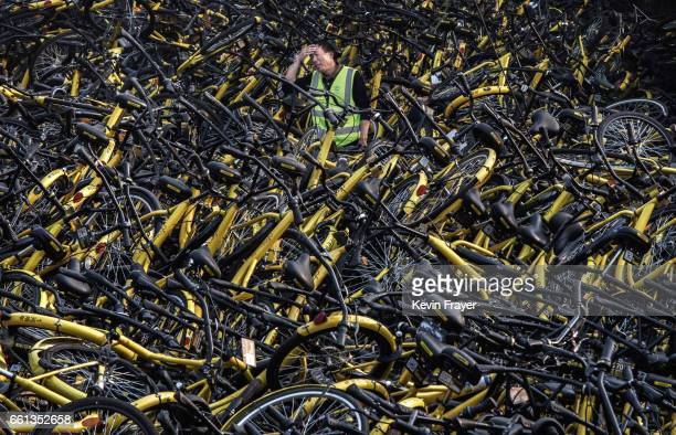 Chinese mechanic from bike share company Ofo Inc stands amongst a pile of thousands of damaged bicycles in need of repair that were pulled off the...