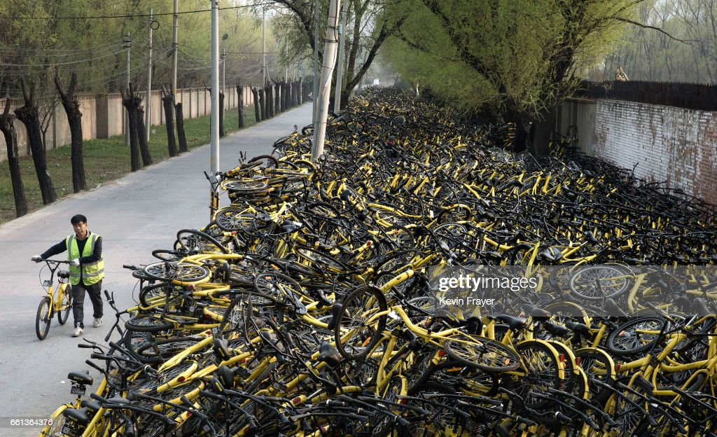 A Chinese mechanic from bike share company Ofo Inc. wheels a fixed bicycle past thousands of damaged bicycles in need of repair that were pulled off the streets where they are kept at a repair depot for the company on March 29, 2017 in Beijing, China. The popularity of bike shares has exploded in the past year with more than two dozen providers now battling for market share in major cities across China. The bikes are hailed as an efficient, cheap, and environmentally-friendly solution for commuters, where riders unlock the stationless bicycles using a mobile phone app, drop them anywhere for the next user, and spend as little as 1 yuan ($0.15) per hour. Given the bikes have several users a day - some of them inexperienced riders who swerve into traffic - they are often damaged, vandalized, or abandoned. Companies like Ofo routinely collect the battered two-wheelers and bring them to a makeshift depot that is part repair shop, part graveyard where they are either salvaged or scrapped. The bike shares are powering a cycling revival of sorts in a country once known as the 'Kingdom of Bicycles'. In the early years of Communist China, most Chinese aspired to own a bicycle as a marker of achievement. When the country's economic transformation made cars a more valued status symbol, the bicycle - a Chinese cultural icon - was mocked as a sign of backwardness.The bike share craze is also a boon for manufacturers who are now mass producing over a million bikes a month to meet demand, and the number of shared bike users will reach 50 million in China by the end of the year, according to Beijing-based BigData Research. Not everyone is cheering the revival though, as municipal officials are drafting new regulations to control the chaotic flood of bicycles on streets and sidewalks.