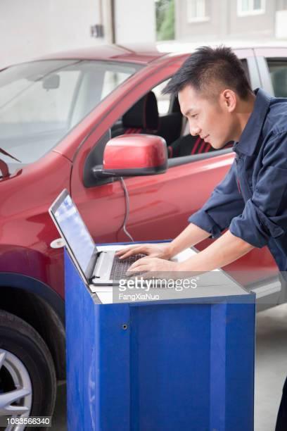 Chinese mechanic working on laptop