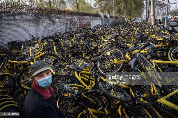 Chinese mechanic works amongst damaged bicycles from the bike share company Ofo Inc as they are piled up at a repair depot for the company on March...