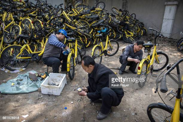 Chinese mechanics work work on damaged bicycles from the bike share company Ofo Inc at a repair depot for the company on March 30 2017 in Beijing...