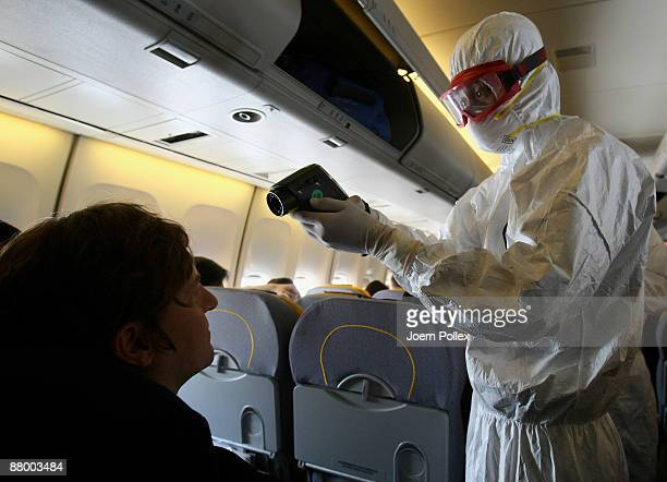 Chinese medical staff checks the body temperature of an air passenger after landing inside a airplane at Pudong International airport on May 27 2009...