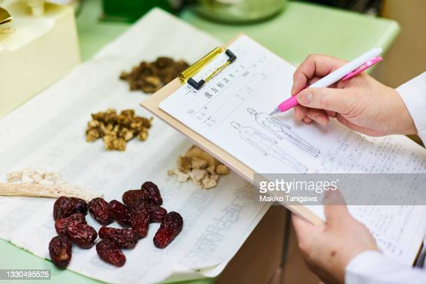 chinese medicine doctor writing in medical records - saitama prefecture stock pictures, royalty-free photos & images