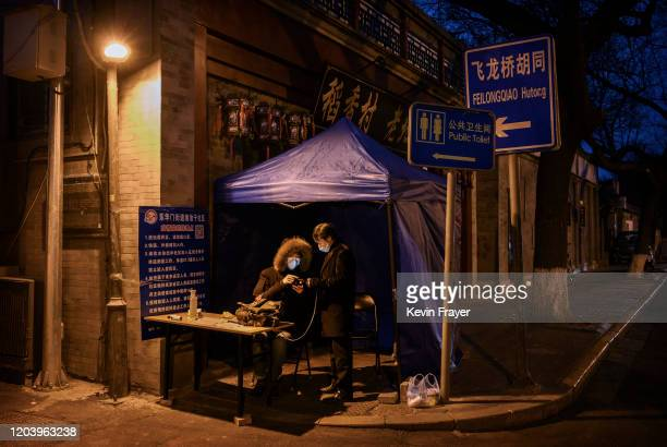 Chinese member of the local neighbourhood committee wears a protective mask as he checks the identification of a man arriving back to a hutong area...