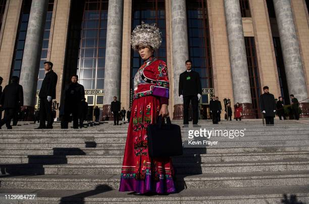 Chinese member of the Miao minority waits on the steps as she arrives for the third plenary session of the National People's Congress at The Great...