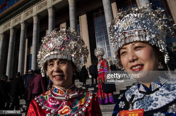 Chinese members of the Miao minority wait on the steps as they arrive for the third plenary session of the National People's Congress at The Great...