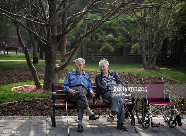 Chinese men chat as they watch women dance at Ritan Park on June 12 2016 in Beijing China Ritan meaning 'sun altar' is among the oldest parks in...