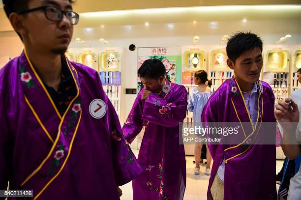 Chinese men dressed in traditional dress prepare for a competition during the Qixi Festival or Chinese Valentine's Day in Shanghai on August 28 2017...