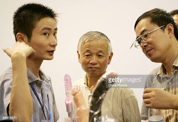 Chinese men listen to the introduction of an exhibition worker as they look at sex toys at the AdultCare Expo at the International Exhibition Center...