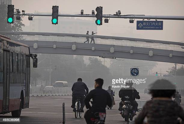 Chinese men walk across a footbridge during a polluted morning on October 17 2015 in Beijing China As a result of industry the use of coal and...