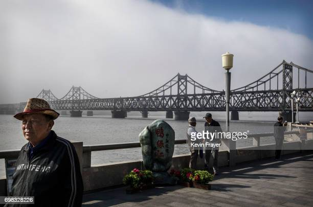 Chinese men walk on the boardwalk near the Friendship Bridge in the border city of Dandong Liaoning province northern China across from the city of...