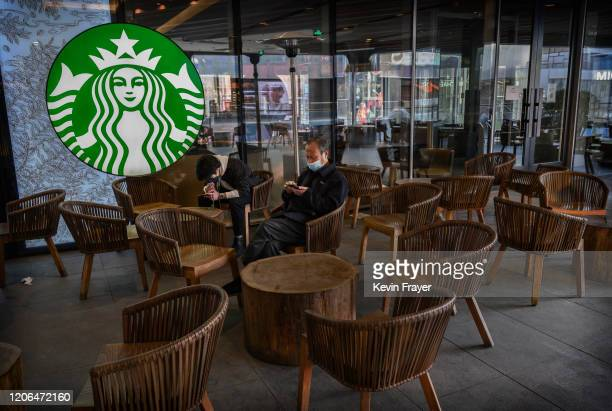 Chinese men wear protective masks as they sit in a nearly empty Starbucks in Sanlitun on March 10, 2020 in Beijing, China. The number of cases of the...