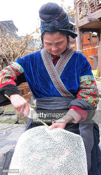 Chinese Miao minority woman in Langde Guizhou Province crochets a handmade fishing net