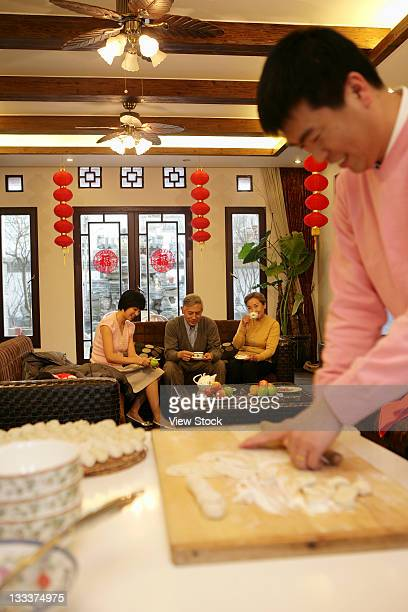 Chinese mid adult man making Chinese dumpling on New Years Eve