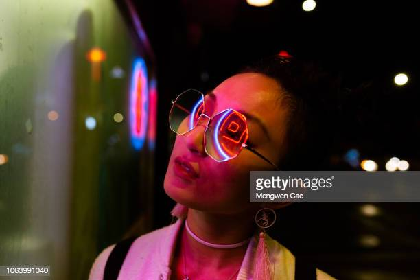 portrait of young woman under neon light - oficio creativo fotografías e imágenes de stock