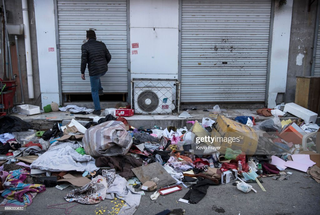 A Chinese migrant worker from Jiangxi closes the shutters on his shop after being evicted on December 4, 2017 in the Daxing District of Beijing, China.Thousands of migrant workers have been forcibly evicted in recent weeks in a sweeping government safety campaign following a deadly fire at a housing settlement. Many migrants, who came to Beijing from poor rural areas to find employment, say they were given little notice to leave and cannot afford to move somewhere else. The government's plan to demolish the buildings was actually announced in a 2015 strategy to reduce and cap the capital's population, but the mass evictions were accelerated after the fire and have stirred public backlash. The migrant population typically work in jobs such as construction, sanitation, and deliveries that have effectively built Beijing and keep it running. Some companies announced assistance and temporary housing for employees who have been affected, but many migrants say they have little choice but to move back to their hometowns.