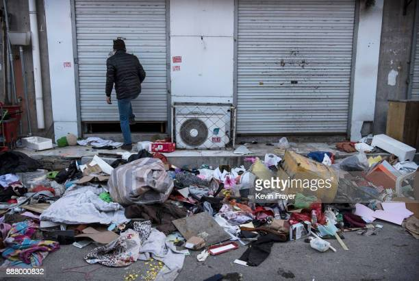 Chinese migrant worker from Jiangxi closes the shutters on his shop after being evicted on December 4 2017 in the Daxing District of Beijing...