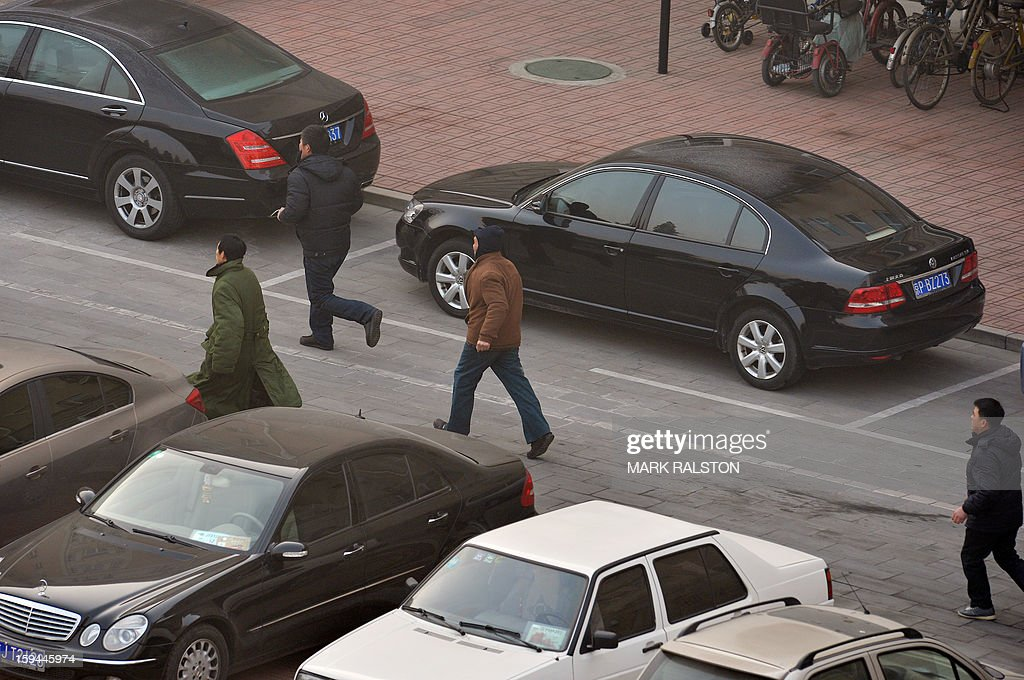Chinese migrant workers run to the residence of a construction firm boss after their group of up to 50 migrant workers stormed past security at the Qijiayuan Diplomatic Compound to protest against what they claim is an unpaid new year bonus, in Beijing on January 14, 2013. Labour unrest and disputes are common before the Chinese New Year when migrant workers are paid for their full years work in a lump sum before heading home to their famillies in outer provinces of the country. AFP PHOTO/Mark RALSTON