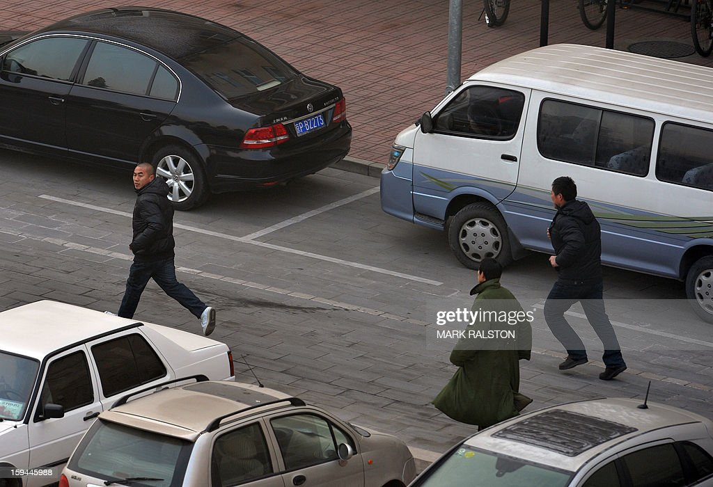 Chinese migrant workers run to the residence of a construction firm boss after their group of up to 50 migrant workers stormed past security at the Qijiayuan Diplomatic Compound to protest against what they claim is an unpaid new year bonus in Beijing on January 14, 2013. Labour unrest and disputes are common before the Chinese New Year when migrant workers are paid for their full years work in a lump sum before heading home to their famillies in outer provinces of the country. AFP PHOTO/Mark RALSTON