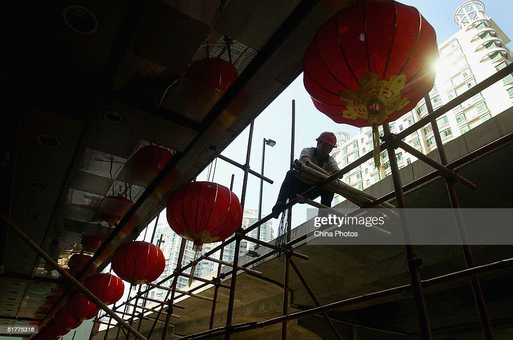 A Chinese migrant works at a construction site November 22, 2004 in Guangzhou, China. A large number of peasant workers temporarily migrated from the countryside to the cities for better income in China in recent years.