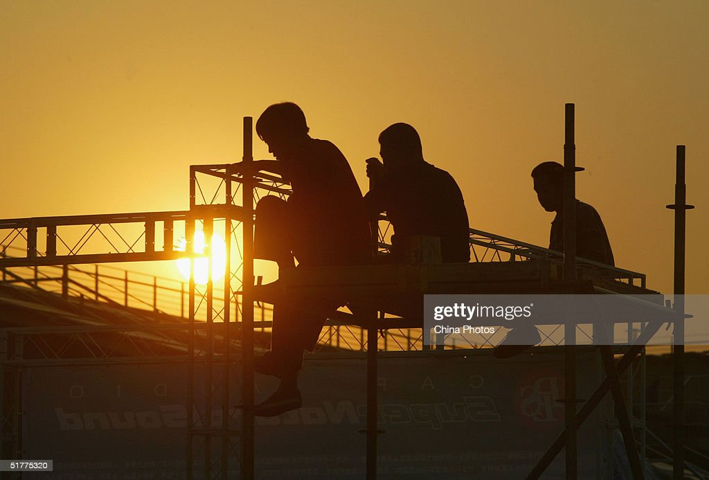 Chinese migrants work at a construction site November 22, 2004 in Guangzhou, China. A large number of peasant workers temporarily migrated from the countryside to the cities for better income in China in recent years.