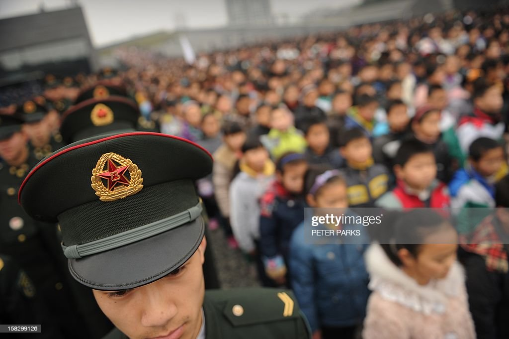 Chinese military personnel (L) and school children (R) attend a a ceremony for victims on the 75th anniversary of the Nanjing massacre at the Memorial Museum in Nanjing on December 13, 2012. Air raid sirens sounded in the Chinese city of Nanjing on December 13 as it marked the 75th anniversary of the mass killing and rape committed there by Japanese soldiers -- with the Asian powers' ties at a deep low. AFP PHOTO/Peter PARKS