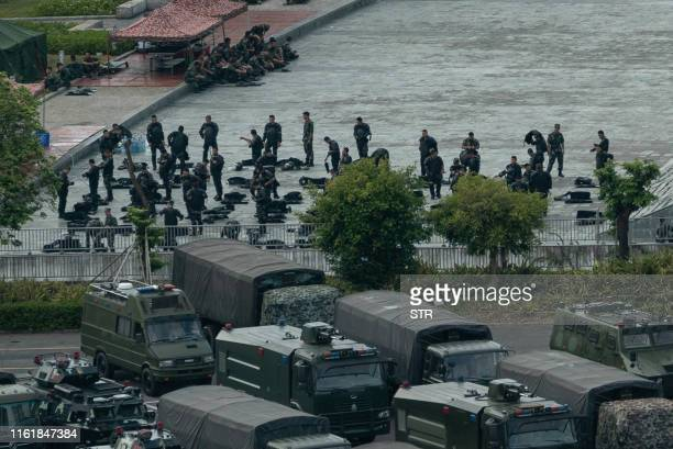 Chinese military personnel gather near parked trucks and armoured personnel carriers at the Shenzhen Bay stadium in Shenzhen bordering Hong Kong in...