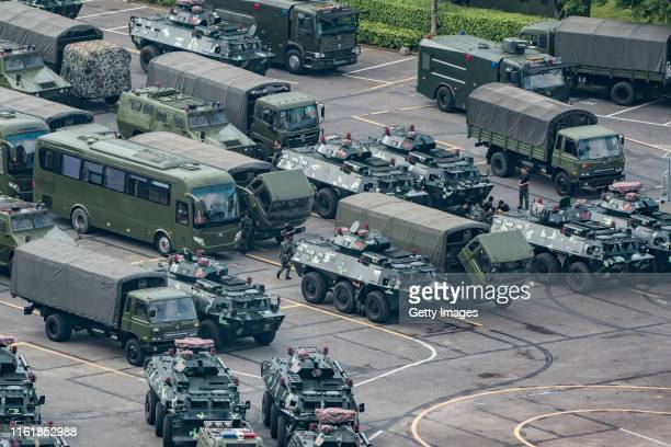 Chinese military personnel maintain trucks and armoured personnel vehicles parked outside the Shenzhen Bay stadium on August 16 2019 in Shenzhen...
