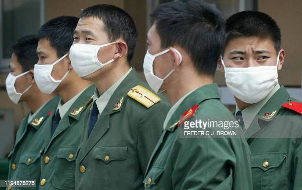 Chinese military personnel stand guard at the Severe Acute Respiratory Syndrome facility of the Xiaotangshan hospital 07 May 2003 on the outskirts of...