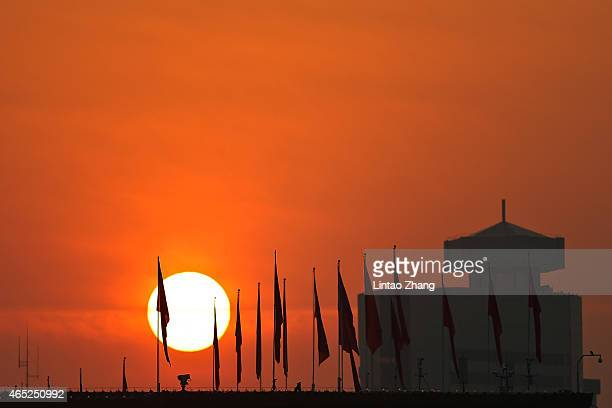 Chinese military personnel watch over Tiananmen Square from a rooftop across from National Museum before the opening session of the annual National...