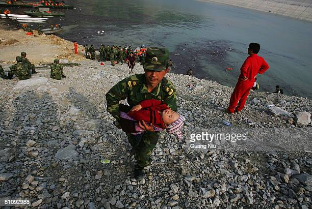 Chinese military soldier transfer a baby from a boat to land after the baby has been brought from Yingxiu county on May 15 2008 in Sichuan province...
