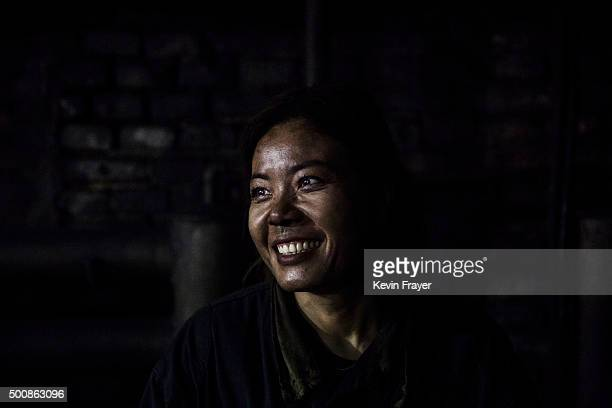A Chinese mine worker smiles as she is covered in coal dust as she sorts coal for quality at a mine on November 25 2015 in Shanxi China A history of...
